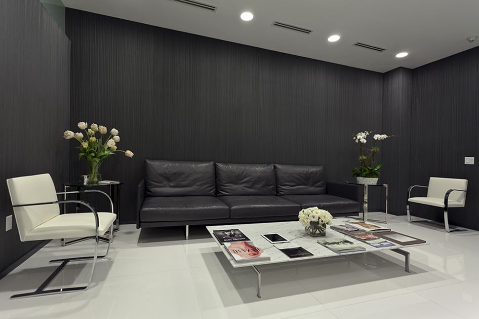 Waiting room of Dr. Herman's office with a black couch and white chairs